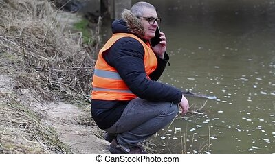 Environmental inspector talking on smartphone near the river...