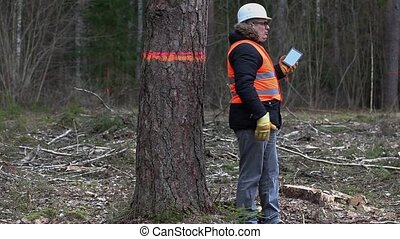 Angry Forest inspector talking on smartphone near last tree...