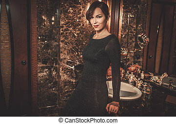 Beautiful well-dressed woman in luxury bathroom interior