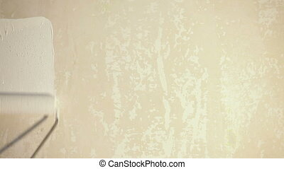 painting interior wall of home with paint roller.