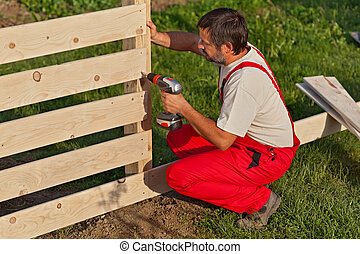 Man building a wooden fence