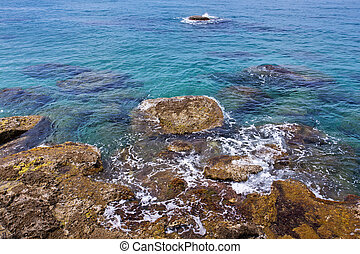 Clear blue sea with rocky shore in the mediterranean area