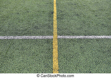 Detail of crossed yellow and white lines on football playground. Lines in a soccer field made from green granule rubber