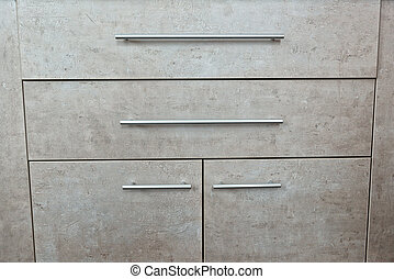 Detail of wooden grey chest of drawers and door in a room