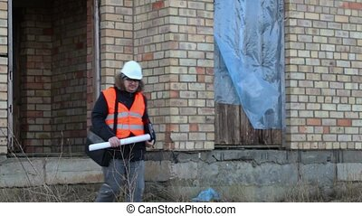 Building inspector checking documents near the building