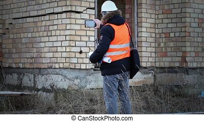 Building inspector filmed with tablet PC near the building