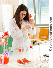 Chemist pipetting substances - Young researcher examining in...