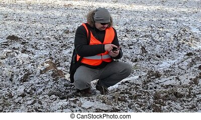 Farmer checking frozen field in winter