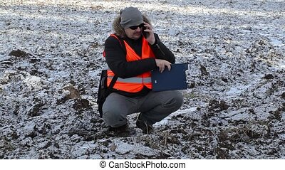 Farmer using tablet PC on plowed,frozen field with snow in...