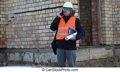 Building inspector with documents checking the building