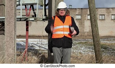 Angry Engineer with documentation near powerline