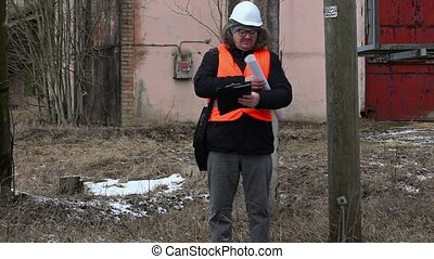 Engineer with documentation near powerline