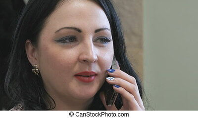 Business lady talks on the phone in cafe