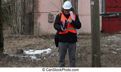Engineer checking documentation near powerline