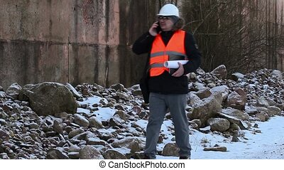 Engineer with smartphone and documentation