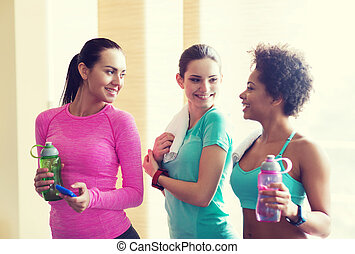 happy women with bottles of water in gym - fitness, sport,...