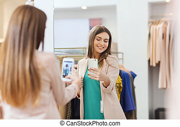 woman taking mirror selfie by smartphone at store -...