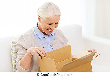 happy senior woman with parcel box at home - age, delivery,...