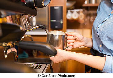 close up of woman making coffee by machine at cafe -...