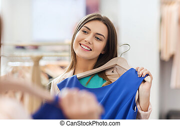 happy woman with clothes at clothing store mirror -...