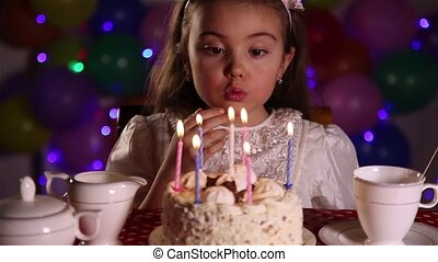 Little girl blowing out the candles of Happy Birthday cake