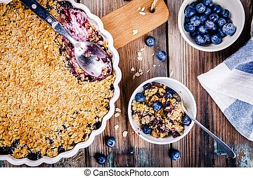 homemade blueberry crumble with oatmeal on wooden table