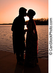 Couple kissing - Indian wedding couple kissing near the...