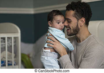 Cuddles with daddy - Young father sitting on his bed,...