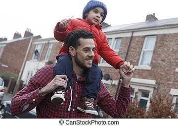 Young father carrying his son on his shoulders as he walks...