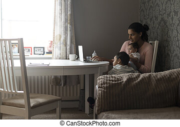 Watching cartoons on mums laptop - Young mother keeping her...