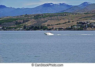 A white powerboat is speeding across the deep blue lake...