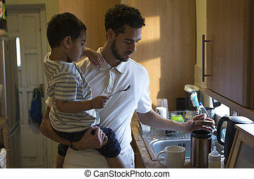Helping daddy make tea - Young father making a cup of tea...