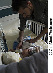 Feeding baby before naptime - Young father feeding his son a...