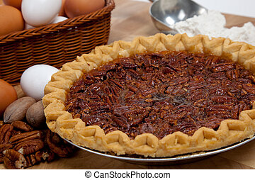 Homemade pecan pie with ingredients - A homemade pecan pie...