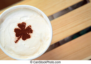 take away cup with shamrock symbol on coffee skin