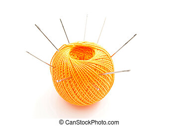 yellow ball of thread with needles