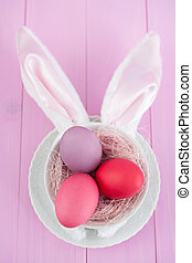 Easter bunny ears costume with Easter eggs on pink wooden...