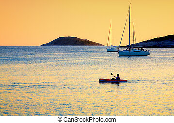 Kayaker - A lone kayaker passes by moored sailboats near an...