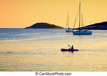 Kayaker - A lone kayaker passes by moored sailboats near an...