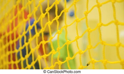 Children play volleyball. Yellow mesh closeup