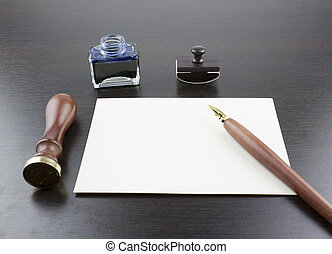 Pens, ink pot, papyrus and blotting paper on a brown table