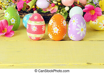 Easter eggs and flowers on a sunny yellow background.