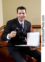 Businessman on couch looking up holding notebook