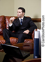 Businessman working on couch thinking in office