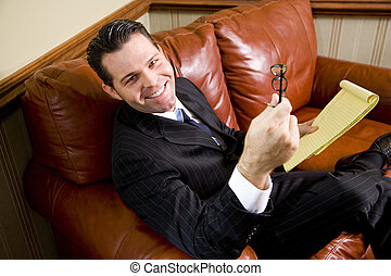 Happy businessman sitting on leather couch looking up