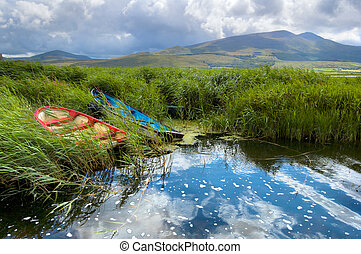 Fishing boats in a lake in County Kerry, Ireland - Colorful...
