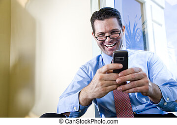 Happy businessman texting on mobile phone - Happy male...