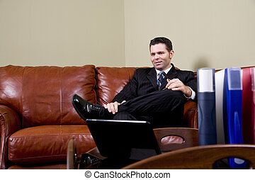 Businessman sitting on leather couch in office