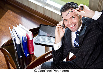 Happy businessman on mobile phone in office