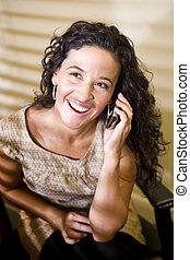 Pretty Hispanic woman talking on a mobile phone